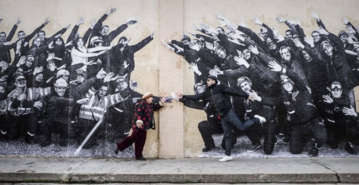 visages-villages-2017-002-agnes-varda-and-jr-reaching-across-wall-with-grafitti